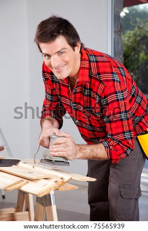 A man looking at the camera holding an electric sander - stock photo