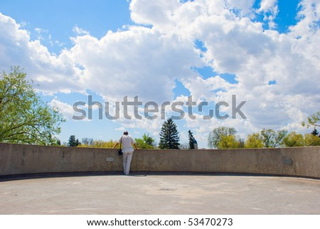 A man looking at the landscape from the outlook - stock photo