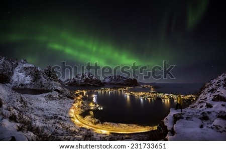 A man looking at the northern lights over Reine, Lofoten islands, Norway - stock photo