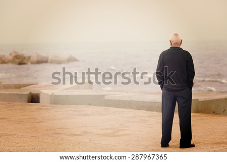 A man looking at the sea on the dock. Image has a vintage effect. - stock photo