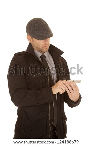 A man looking down at his pistol with a serious expression. - stock photo