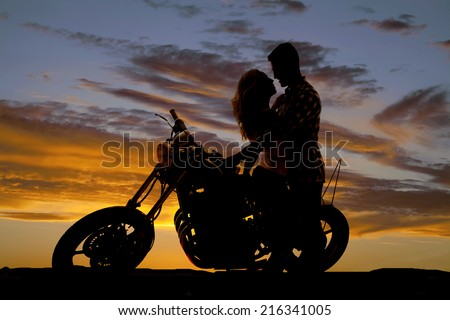 A man looking down at his woman, as she sits on a motorbike, looking into her eyes. - stock photo