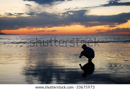 A man looking into his reflection during a sunset. - stock photo