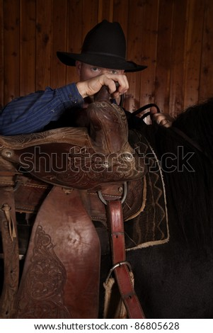 A man looking over his saddle on his horse. - stock photo