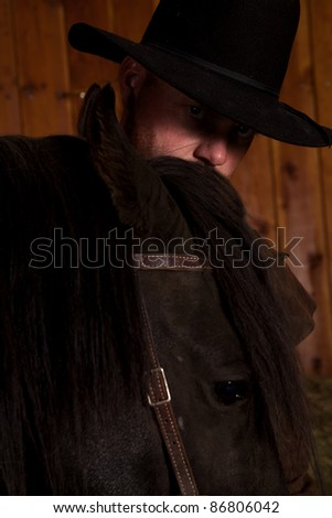 A man looking over the top of his horses head. - stock photo