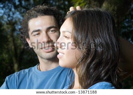 A man looks lovingly at his girlfriend as he brushes away her hair. Both look happy and relaxed. Horizontally framed photograph.