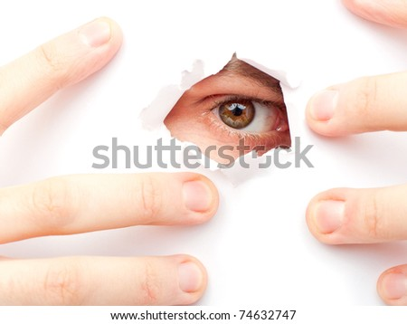 A man looks out a large hole in the white wall - stock photo