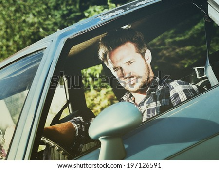 A man looks out his window while driving a blue car.