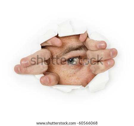 A man looks through a hole in the paper - stock photo