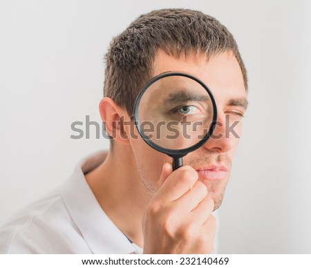 A man looks through a magnifying glass