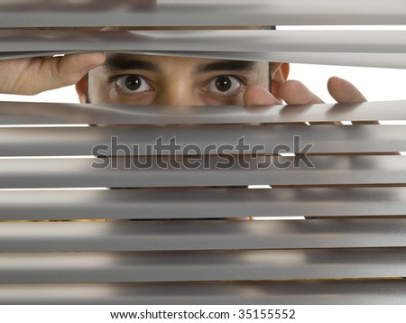 A man looks to the camera through the blinds.