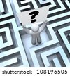 A man lost in a maze or labyrinth holds a question mark sign to seek help in finding a way out or getting an answer or solution to a problem or trouble - stock photo