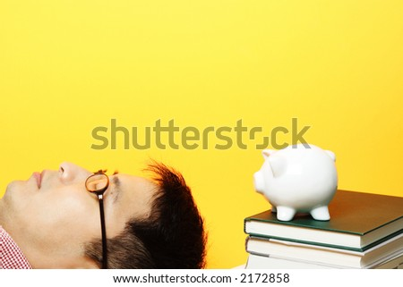 A man lying next to a piggy bank on top of stack of books - stock photo