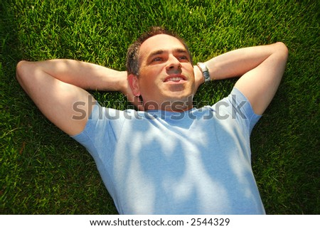 A man lying on green grass relaxing