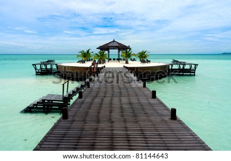 A man-made walkway Kapalai island with exotic tropical resort - stock photo
