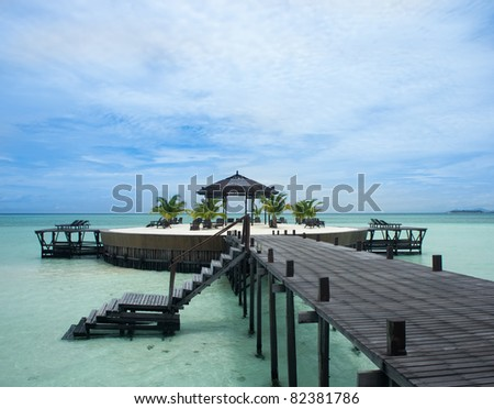 A man-made walkway Kapalai island with exotic tropical resort - stock photo