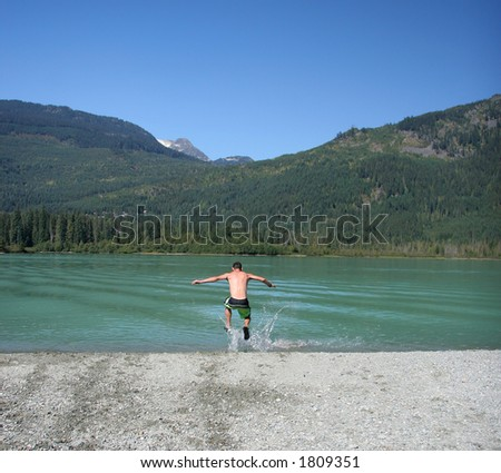 A man makes a mad dash into freezing cold glacier water. - stock photo