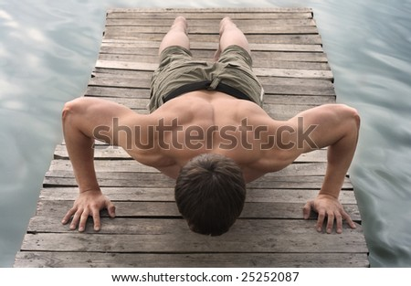 A man makes pushing up on the old wooden brige - stock photo