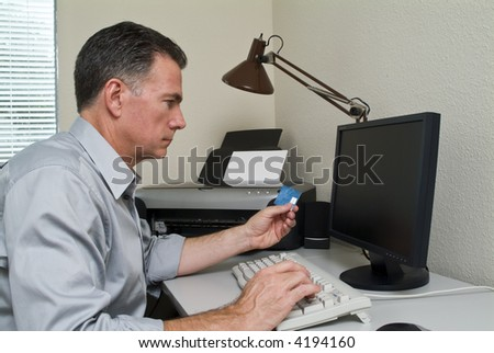 A man making a credit card purchase online. - stock photo