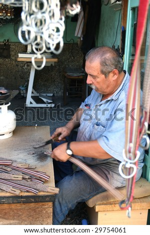 a man making halter for horses with a knife