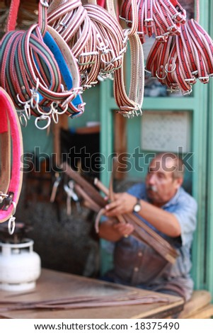 a man making halter for horses with shallow depth of field