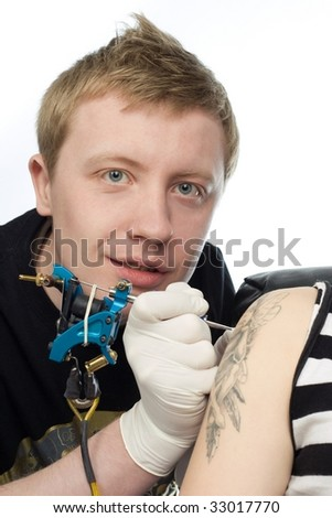 A man  making procedure of tattoo on a shoulder - stock photo