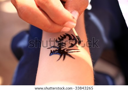 A man making temporary henna tattoo - stock photo