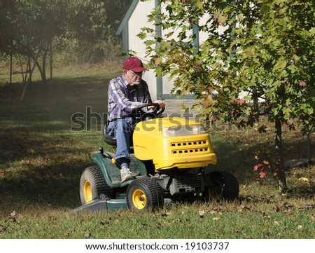 A man mowing his lawn with a lawn tractor.