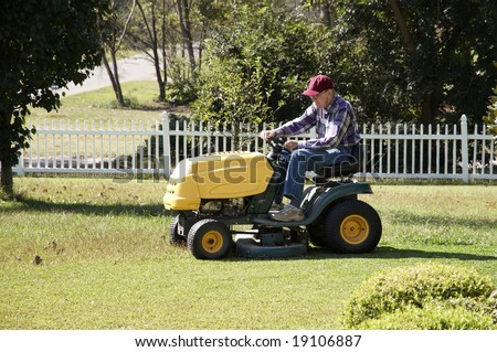 A man mowing his lawn with a riding mower.
