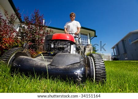 A man mowing the front lawn with focus on the front - stock photo
