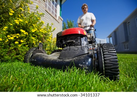 A man mowing the front lawn with focus on the front wheel - stock photo