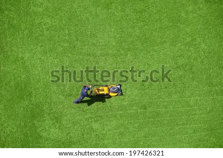 A man mowing the lawn - stock photo
