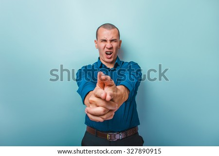 a man of European appearance thirty years shows a finger gun on black background - stock photo
