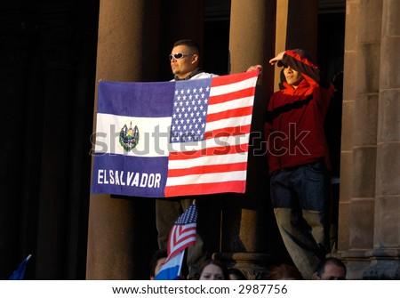 A man of Hispanic heritage displays a half Salvadorian, half American flag at a pro-immigration rally in Boston, Massachusetts. - stock photo