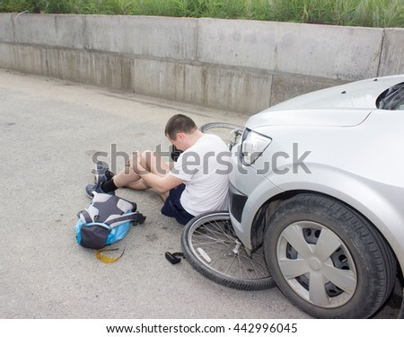 a man on a bicycle hit by a car and he broke his knee - stock photo