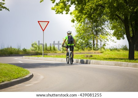 A man on a Bicycle with a backpack riding on an asphalt road in the journey. - stock photo