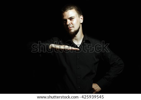 A man on a black background. Man shows the size. Portrait of a Man. Emotional portrait.