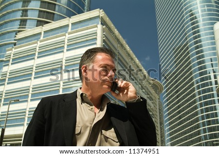 A man on a cell phone with large glass covered high rise office building in the back ground. - stock photo