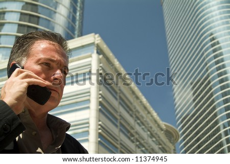 A man on a cell phone with large glass covered office buildings looming in the background. - stock photo