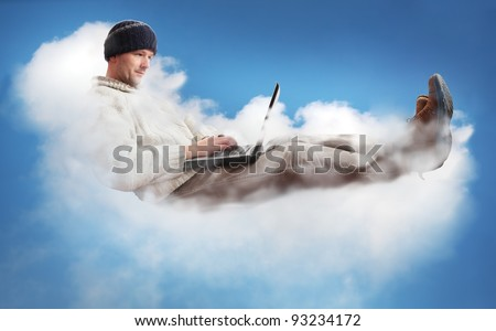 A man on a cloud operating a laptop.  The man is dressed casually to represent the majority of IT workers.  The concept is Cloud Computing - software/computing in the cloud. - stock photo