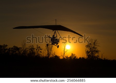 A man on a hang-glider is landing in a field - stock photo