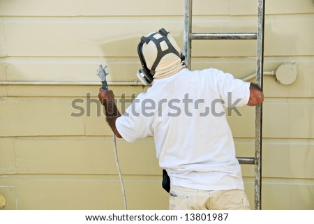 A man on a ladder uses spray gun to paint the exterior of a wooden building - stock photo
