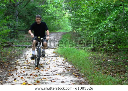 A Man on a Mountain bicycle with a LED flashlight for a headlight riding through the woods with room for your text. - stock photo