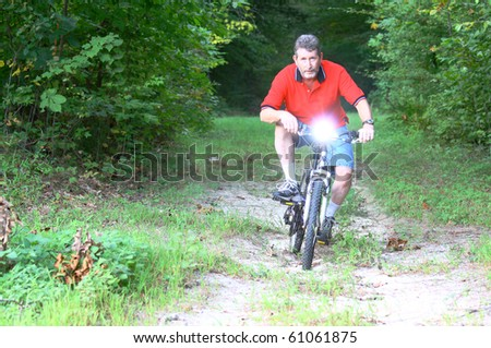 A man on a Mountain bike with a flashlight mounted on the handlebars coming through the woods with room for your text - stock photo