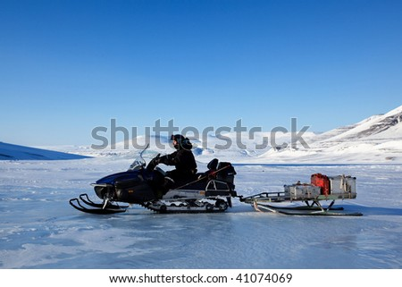 A man on a snowmobile against a winter landscape - stock photo