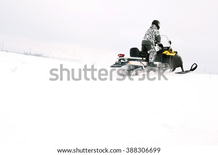 a man on a snowmobile. Winter sports and entertainment.