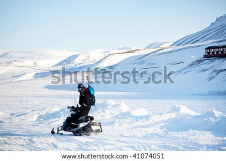 A man on a snowmobile with a gun and shovel for safety