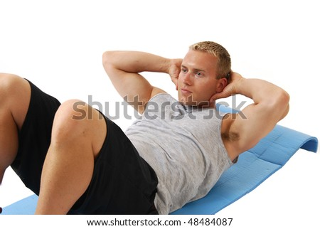 A man on an exercise mat doing situps - stock photo