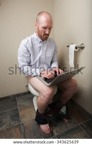 A man on his computer while on the toilet - stock photo