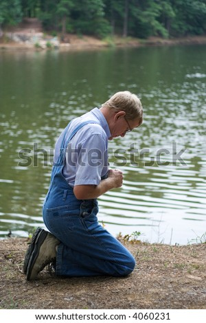 A man on his knees praying beside a lake.